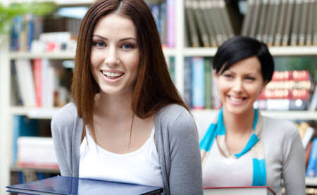 Two beautiful girlfriends carry piles of books at the library photo