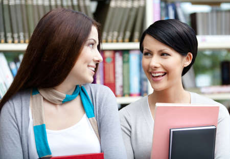 adult intercourse: Two girlfriends with books look at each other standing against bookshelves at the library