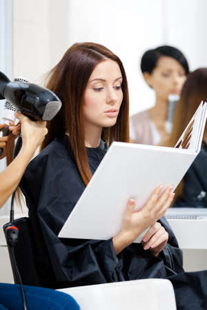 Beautician does hair style for woman in hairdressing salon. Concept of fashion and beauty photo