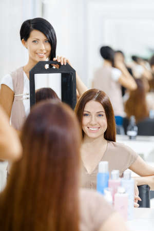 Hair stylist showing the ready hairstyle of the female client in mirror. Concept of fashion and beauty photo