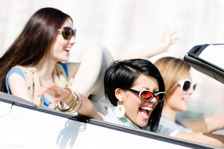 Group of happy girls in the auto. Little trip of teenage ladies photo