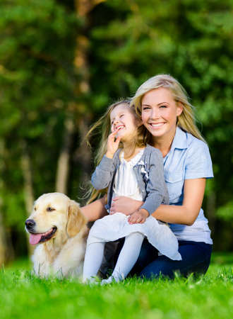 vertical format: Mother and daughter with dog sitting on the green grass at the summer park