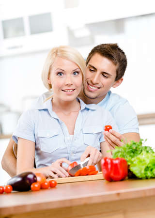 Married couple preparing breakfast sitting together at the breakfast table full of vegetables photo