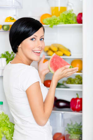 Girl takes watermelon from the opened fridge full of vegetables and fruit. Concept of healthy and dieting food photo