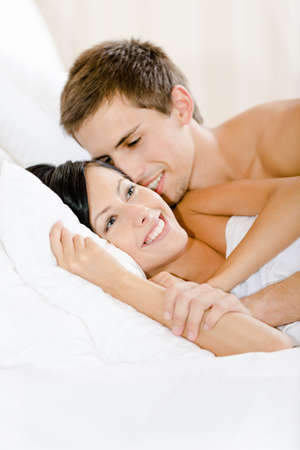 Man lying in bed-room with white linen embraces woman. Concept of love and affection photo