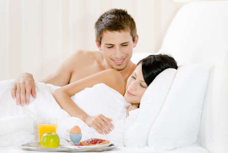 Lying man serves lady breakfast in bed. Concept of love and affection photo