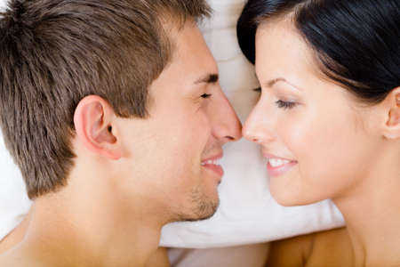 Headshot of couple lying in bed, top view. Concept of love and affection photo