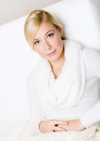 Portrait of pretty blond woman sitting on the white sofa Stock Photo - 26692532