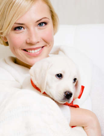 Woman holding puppy of labrador with red ribbon on the neck Stock Photo - 26692564