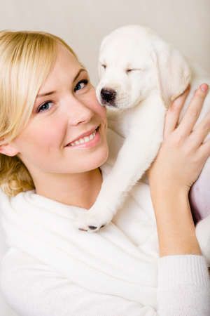 Woman keeping white puppy of Labrador with eyes shut near her face Stock Photo - 26692566