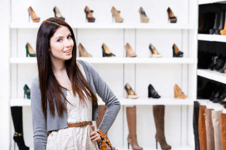 high heeled shoe: Portrait of woman in shopping center in the section of female shoes. Concept of consumerism and stylish purchase Stock Photo