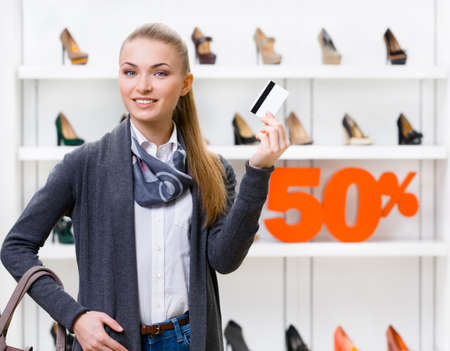 Girl showing credit card in footwear shop with great variety of stylish shoes and 50% sale photo