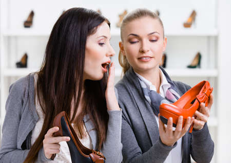 Salesperson offers stylish pumps for the female customer in the shopping center photo