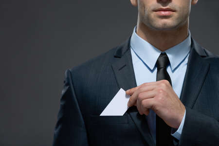 male parts: Part of body of man who pulls out business card from the pocket of business suit, copyspace