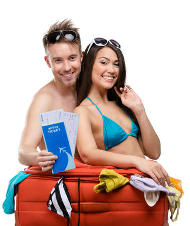 Couple packs suitcase and tries on clothing for travel, isolated on white. Concept of romantic vacations and lovely honeymoon photo