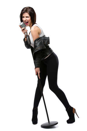 full metal jacket: Full-length portrait of rock singer wearing leather jacket and handing static mic, isolated on white. Concept of rock music and rave Stock Photo