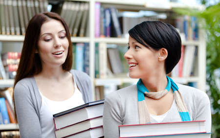 adult intercourse: Two girlfriends carry piles of books at the library