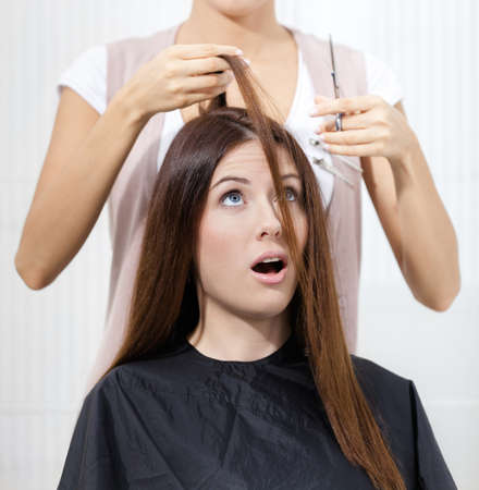 hairdress: Hairdresser cuts hair of woman in hairdress salon. Concept of fashion and care Stock Photo