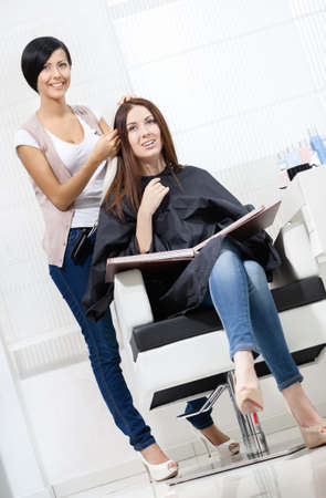 Beautician tries lock of dyed blond hair on the client sitting on the chair in the hairdress salon