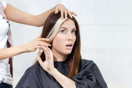 Hairdresser tries lock of dyed blond hair on the client sitting on the chair in the hairdress salon photo