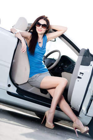 Pretty woman in sunglasses sits in the cabriolet with door opened photo