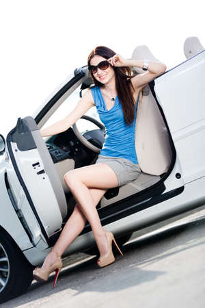 Pretty woman in sunglasses sits in the white car with door opened photo