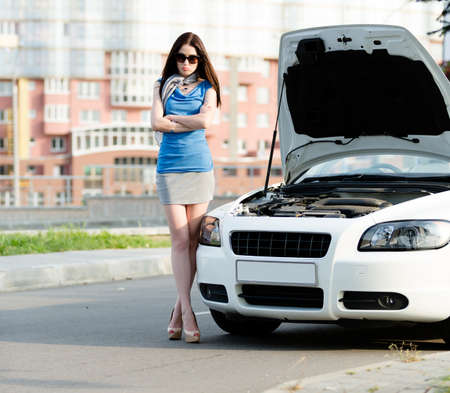 street shots: Woman with the arms crossed near the opened hood of the broken car waiting for assistance Stock Photo
