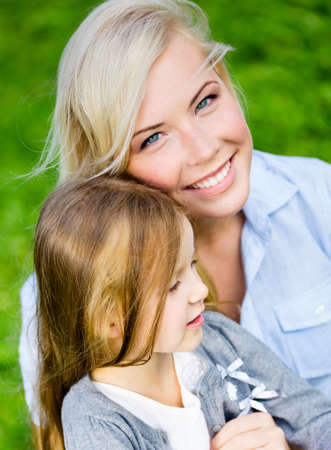 Mother and daughter embrace each other sitting on the grass. Leisure time of happy family photo