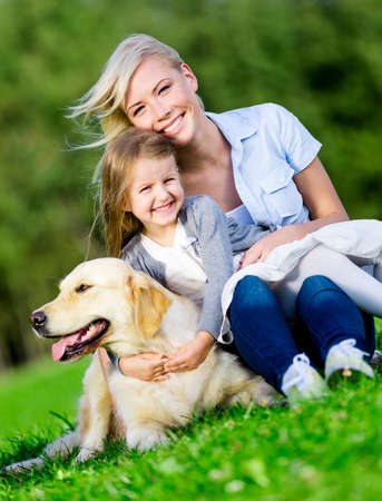 Mother and daughter with golden retriever sitting on the green grass at the summer park photo