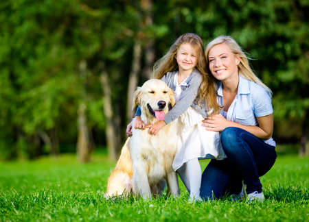 Mother and daughter with labrador retriever sitting on the grass at the summer park photo