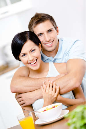 Male hugs his smiley girlfriend in the kitchen photo