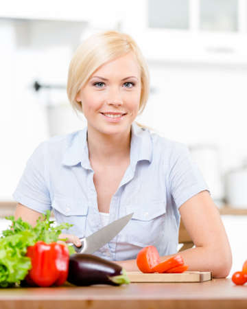 Woman slices vegetables for salad sitting at the kitchen table photo