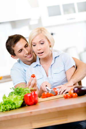 Couple preparing breakfast sitting together at the breakfast table full of vegetables photo