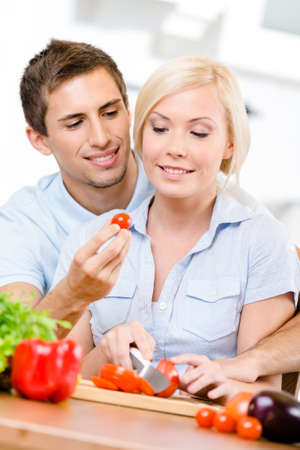 Young couple preparing breakfast sitting together at the breakfast table full of vegetables photo