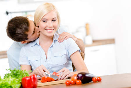 Man kisses young woman while she is cooking sitting at the kitchen table full of vegetables photo