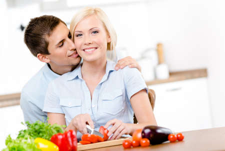 Man kisses female while she is cooking sitting at the kitchen table full of groceries photo