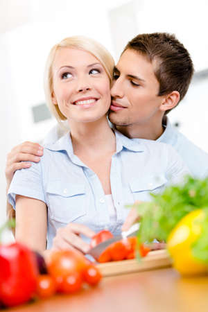 Man kisses young woman while she is cooking sitting at the kitchen table full of groceries photo