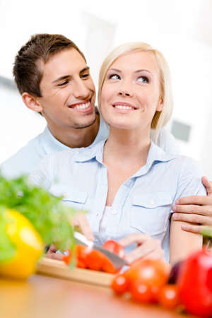 Man embraces woman while she is cooking sitting at the kitchen table full of vegetables photo