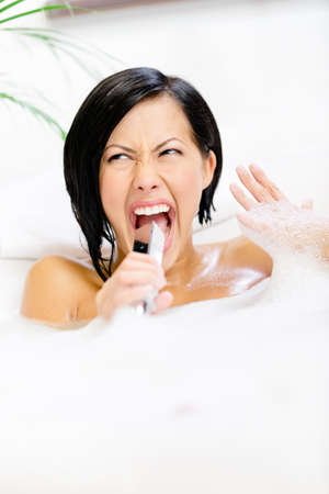 Woman lying in bathtub with suds plays with shower head like microphone and relaxes photo
