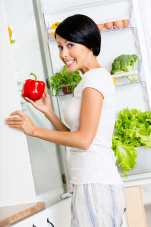 Girl takes red pepper from the opened fridge full of vegetables and fruit. Concept of healthy and dieting food photo