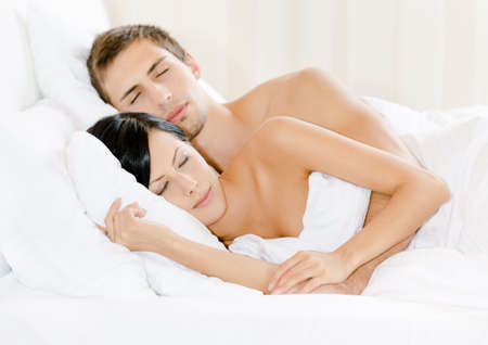 Couple sleeping in bed under white eiderdown photo