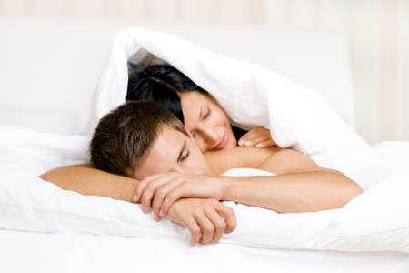 Frau schl�ft auf Mann im Bett mit Decke abgedeckt. Konzept der Liebe und Zuneigung photo