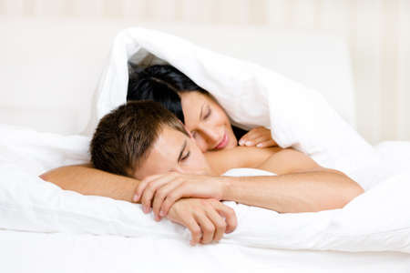Woman sleeps on man in bed covered with blanket. Concept of love and affection photo