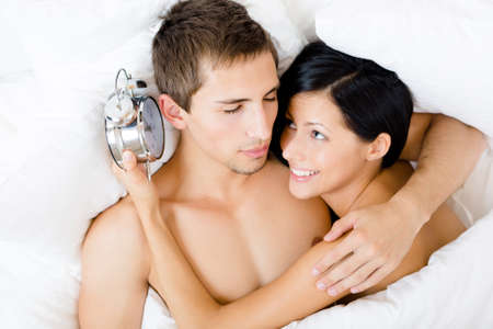 Close up of couple lying in bed-room. Woman holds alarm clock near the ear of man, top view photo