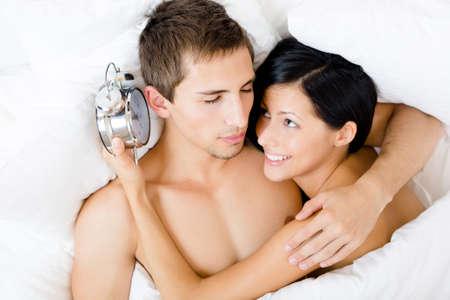 Nahaufnahme von Paar im Bett-Zimmer liegen. Frau h�lt Wecker nahe dem Ohr des Menschen, Ansicht von oben photo