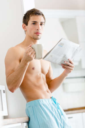 Half-naked man with cup of tea reads newspaper standing near the fridge at the kitchen photo