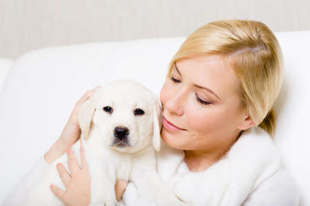 Portrait of woman in white sweater with white Labrador puppy photo