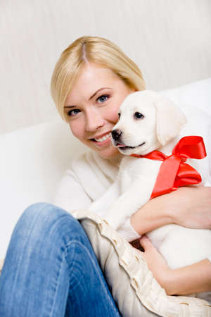 Woman embracing white puppy of Labrador with red ribbon on the neck photo