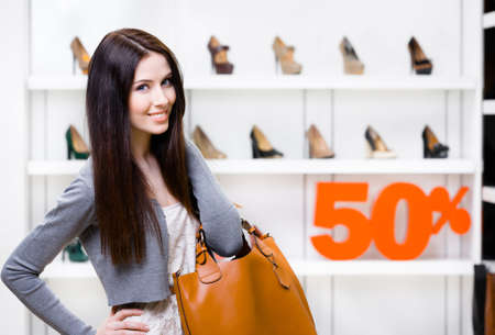 Portrait of woman in shopping center with 50% sale in the section of female footwear. Concept of consumerism and stylish purchase photo