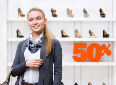 Portrait of woman in shopping center with 50% sale in the section of female shoes. Concept of consumerism and stylish purchase photo